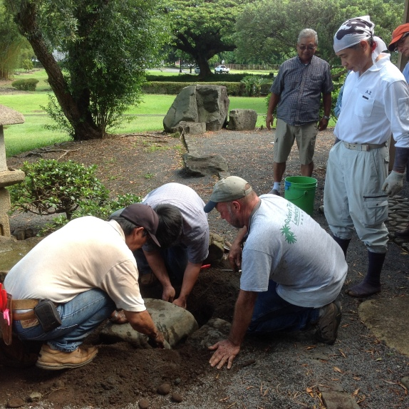 David Tamura and his son Troy and Robert Frost re-set a stone at Takuhiro Yamada's direction